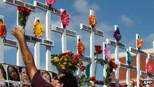 Relative of victims of the Casino Royale attack puts flowers on a cross during the commemoration of the first anniversary of the crime in Monterrey, Mexico, on 25 August 2012