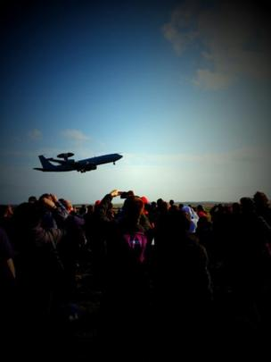 AWACS takes off as a crowd watches