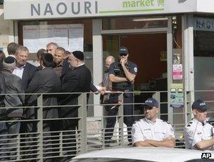 French police, members of the Jewish community and others stand outside the kosher store attacked in Sarcelles, 19 September