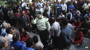 A police officer debates with workers protesting about delayed wages in front of the ministry of industry in Tehran on 14 August