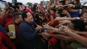 Presidential candidate Hugo Chavez greets supporters during a campaign rally in the district of Catia in Caracas on 17 September 2012.