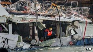 """A fireman inspects the back end of the badly damaged Lamma IV passenger boat after a collision, near the shores of Hong Kong""""s Lamma island on 3 October, 2012 the morning after it was pulled out of the waters following its sinking on 1 October"""