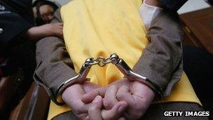 File photo: A crime suspect being handcuffed in China