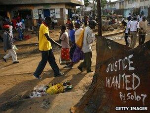 People walk past slogan in Kibera slum, Naoribi in 2008
