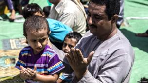A father and son pray together during the Friday prayer in Mualla district, where the port of Aden is located. Photo: Luke Somers