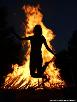 Silhouette of a person in front of a bonfire