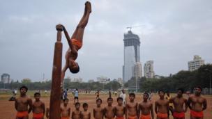 Boy performing a mallakhamb pose