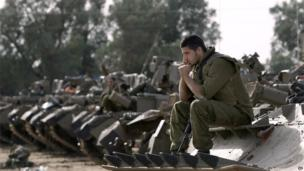 An Israeli soldier sits on the front of one of a line of armoured personnel carriers on the border with Gaza