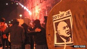 """A protester wears a picture of Maribor's Mayor Franc Kangler, which reads: """"You are finished"""", during a demonstration in Maribor December 3, 2012."""