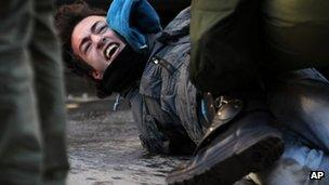 Greek riot police detain a protester in Thessaloniki, 6 December