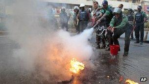 Policemen douse flames during a Jamaat-e-Islami demonstration in Dhaka on 4 December 2012