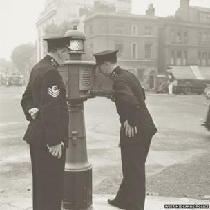 "Two officers with a ""police pillar"" in September 1950"