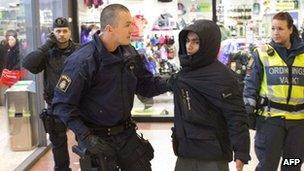 Police restrain a man at a shopping centre in Gothenburg, Sweden (18 Dec 2012)