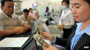 Employees counting money at a bank in Cambodia