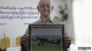 Stanley Coombe poses with picture of Spitfire fighter plane. 9 Jan 2013