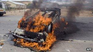 A car belonging to South African newspaper group, Independent Newspapers, burns after being set alight during clashes between striking farm workers and anti-riot police forces on 9 January 2012 in de Doorns