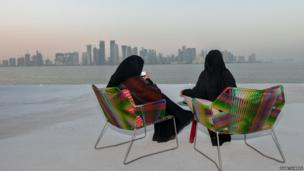 Two Qatari women drinking 'designer' coffee on a winter's evening at the Museum of Islamic Art park overlooking West Bay, Doha.