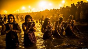 Hindu devotees bathe in the waters of the Ganges in Allahabad, India, 14 January 2013