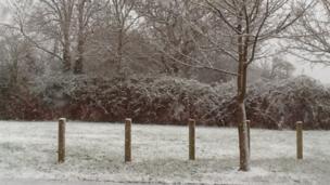 Snow falling outside a house