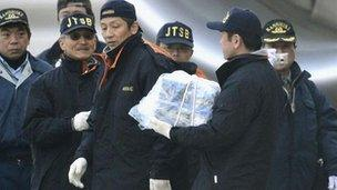 Japanese investigator carries a battery from ANA flight