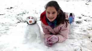 A girl lying in the snow next to a snowdog.