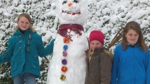 A tall snowman next to three girls.