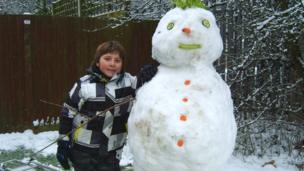 A snowman with vegetable features - a carrot nose and cucumber eyes.