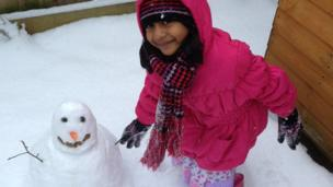 A girl shaking hands with her snowman.