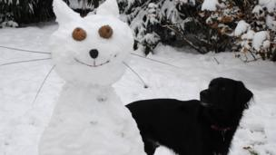 A cat made of snow in a snowy garden. A bewildered dog looks on.