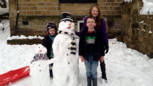 Three children next to their snowmen.
