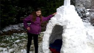 A girl stood beside an igloo.