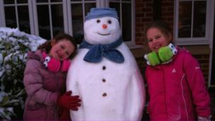 Two girls with a snowman.