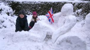 Two children with a snowman.