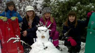 Four children and a snowman.