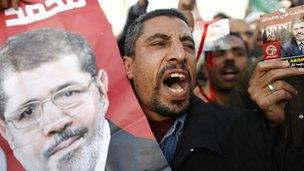 Man at a demonstration holds up a poster of Mohammed Morsy