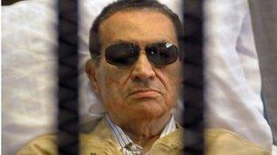 Ousted Egyptian president Hosni Mubarak sits inside a cage in a courtroom in Cairo on 2 June, 2012. This year the verdict in his former trial was overturned and a retrial ordered.