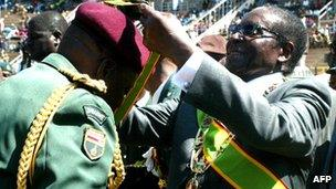 Zimbabwean President Robert Mugabe (R) confers the medal of honour to an army officer at the National Sports Stadium in Harare on 9 August 2011