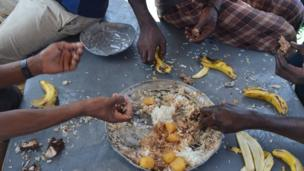 Crew members on the Kenyan fishing vessel eating rich goat stew and bananas