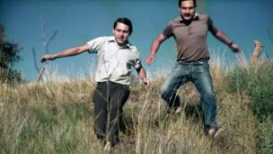 Omar Dario and Mario Alfredo Amestoy running through grass.
