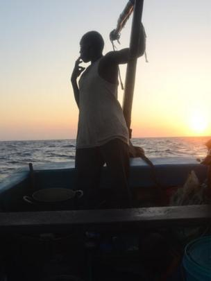 A crewman aboard the Kenyan fishing vessel looks out to sea smoking a cigarette as the sun sets