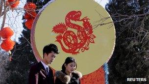 People walk past a Chinese decorative drum with a paper-cutting of a snake ahead of the Chinese Lunar New Year celebrations at Ditan Park in Beijing on 4 February 2013