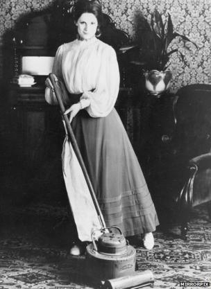 Woman using a vacuum cleaner in the 1920s