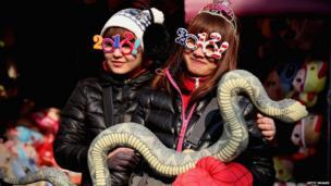 Girls hold snake.