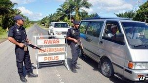 Malaysian policemen check a vehicle near Lahad Datu in Sabah on 14 February 2013