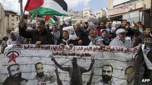 Palestinian protestors wave their national flag and hold portraits of Samer Issawi in East Jerusalem - 15 February