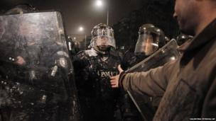 A protester reaches his hand out to a riot police officer