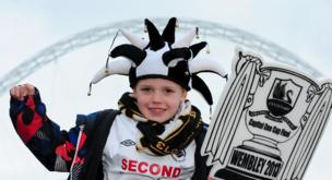 Swansea City fan Cam Warren, seven, shows his support outside Wembley Stadium before the Capital One Cup Final match at Wembley