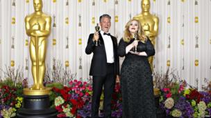 Adele and Paul Epworth pose with Oscars.