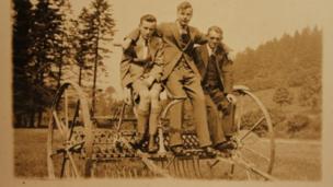 This photo shows three men sitting on farm machinery c1930s