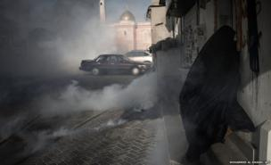 A Bahraini woman runs from cover from tear gas